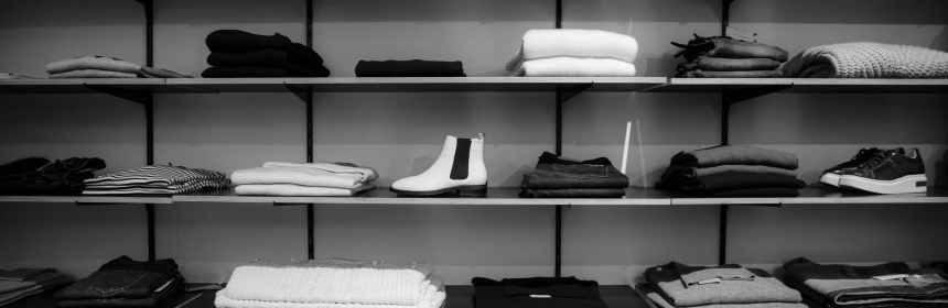 Grayscale photography of assorted apparels on shelf rack